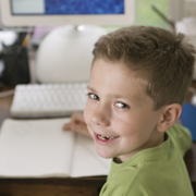 young boy turned around at a computer with a notepad