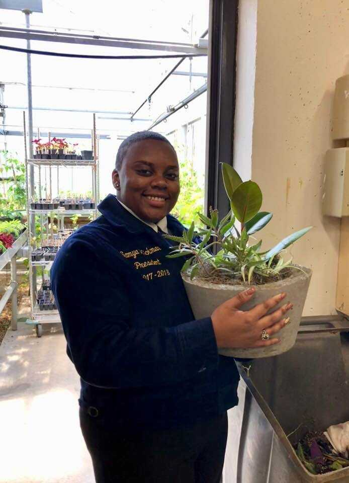 student holding plant