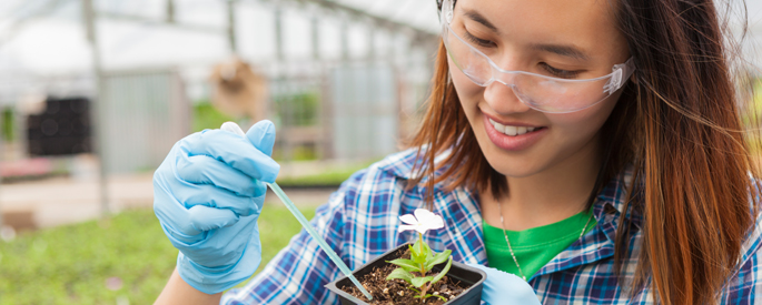student studying botany in greenhouse