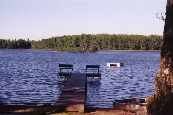 Jag Lake with dock, raft, boat, and view of wooded coastline