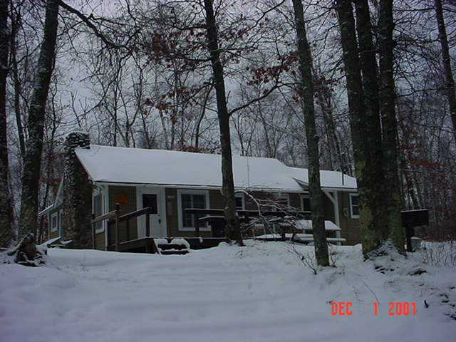 photo exterior of cabin in winter with snow