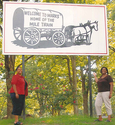 Carolyn Stanford-Taylor and her daughter pointing up at a billboard that says 'Welcome to Marks. Home of The Mule Train.'