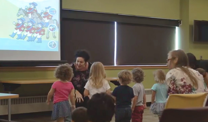 Librarians interacting playfully with children in the front of a large room. Chairs are in the back of the room and a screen is in the front.