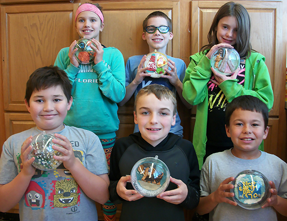 Six students smiling and holding their ornaments.