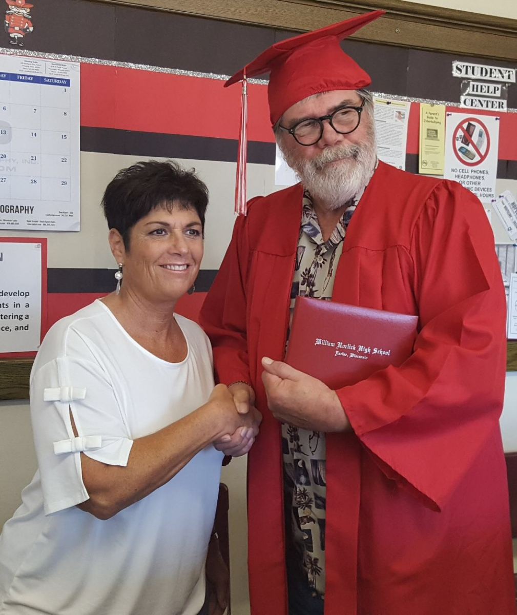 Male Veteran Graduate holding diploma shaking hands with teacher