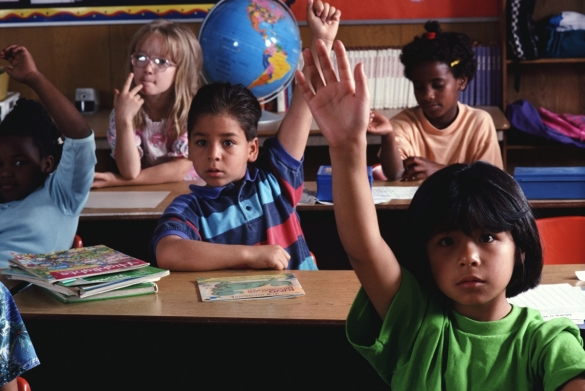 Stock image of a classroom with students raising their hands