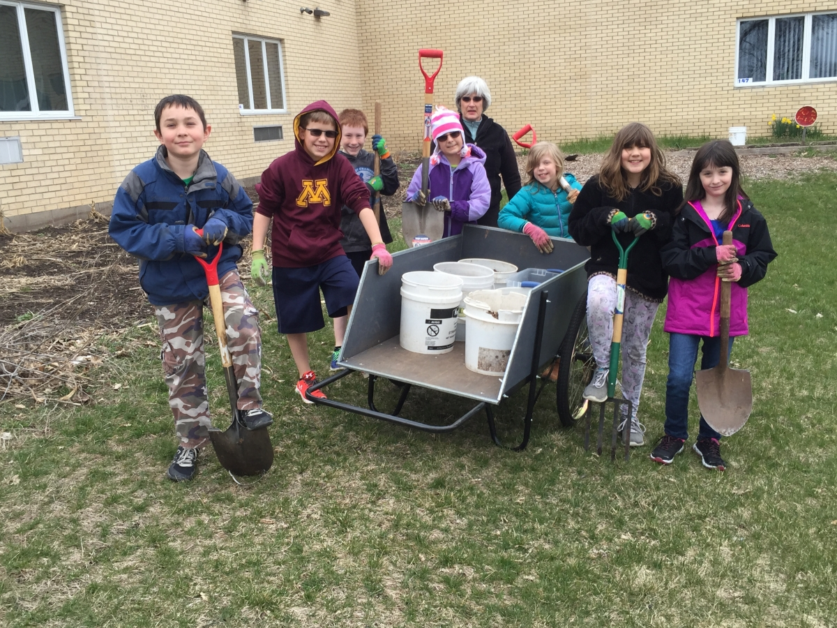 kids with shovels helping teacher with yardwork