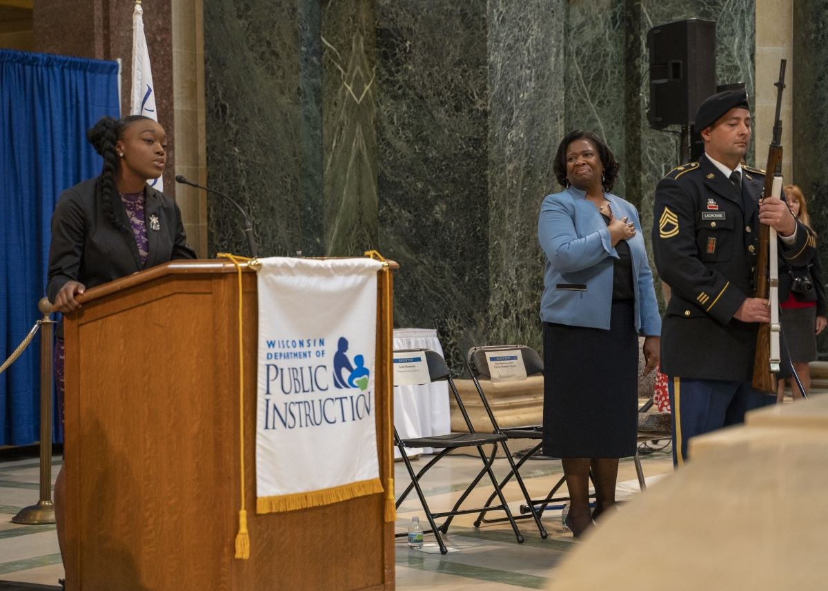 Desiray Meade singing while State Superintendent Carolyn Stanford Taylor looks on with a smile
