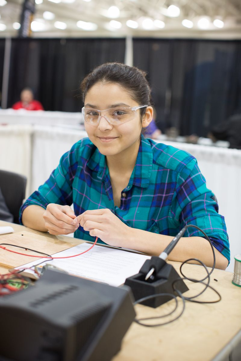 High School girl soldering at competitive event