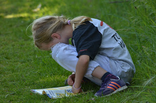 Child reading book in the grass