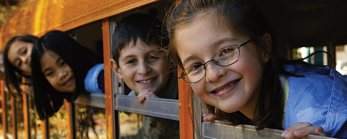 Several children are pictured in the same image as they look out the window of a school bus.