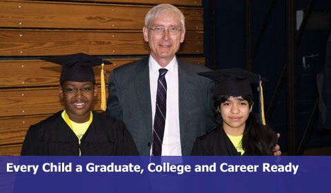 State Superintendent Tony Evers with two children in cap and gowns